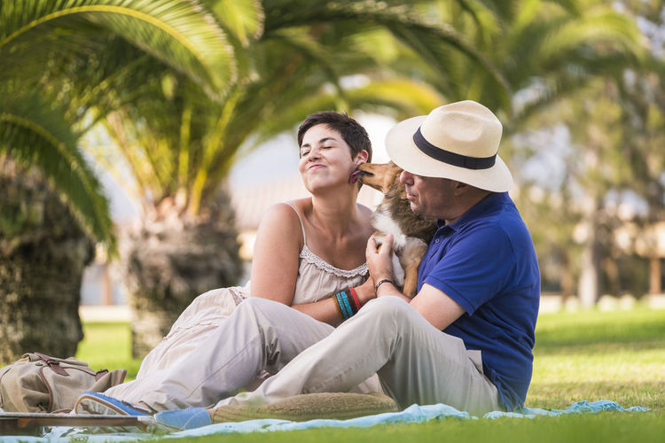 Dog licking woman held by man at public park