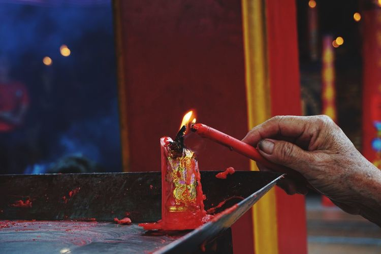 Cropped hand of man holding burning candles in temple