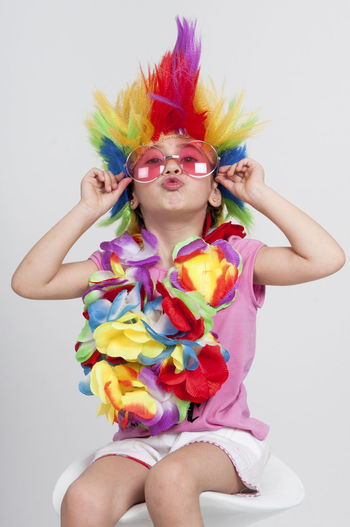 Funny beautiful party little girl in disguise with wig in many colors and pink round sunglasses White Background Front View Studio Shot One Person Childhood Child Multi Colored Indoors  Girls Paint Females Face Paint Leisure Activity Portrait Costume Three Quarter Length Looking At Camera Innocence