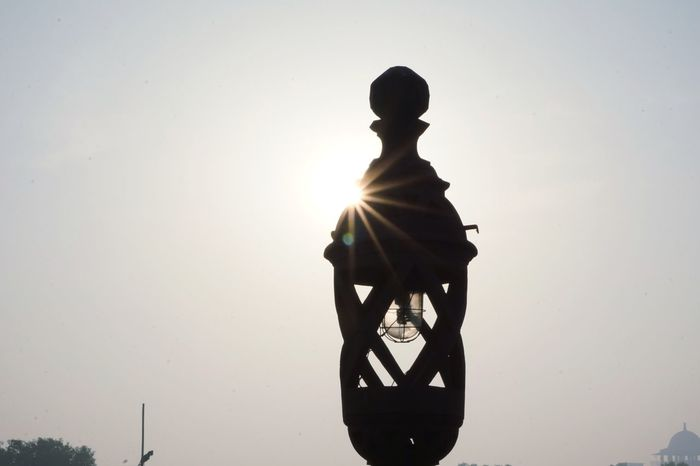 when sun peeps. DelhiMetro NCR Delhidiaries DMRC Sunlight Sunrays SunPeepingThrough Lamp Post Indiagate Delhidiaries Delhi Streets Delhiexplorer No People Sunrise Morning Light Silhouette Adult People Walking Sunlight Outdoors