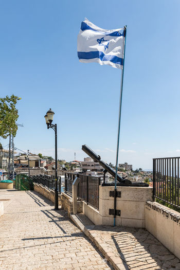 Safed, Israel, September 08, 2018 : The famous Davidka - grenade launcher released by handicraft during the Indepence endWar of Israel and the flag of Israel in the city of Safed. Army Homemade Independence War Of Israel Jewish Memorial Zefat Artillery Weapon Battle Culture Davidka Day Flag Galilee Grenade Launcher Handicraft Hisyory Israel Landmark Monument Mortar Safed Stone Material Street Symbol Travel Destinations