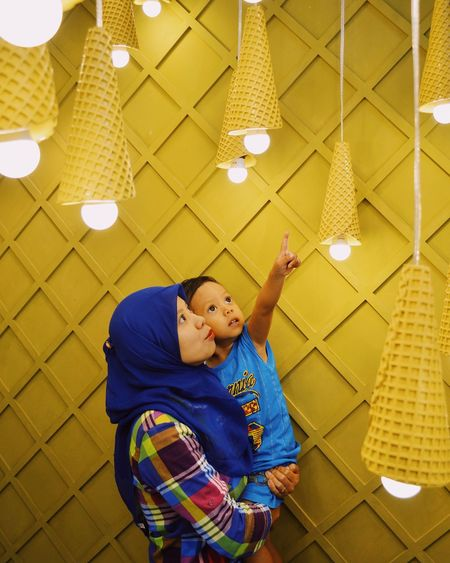Mother and son looking at illuminated pendant lights