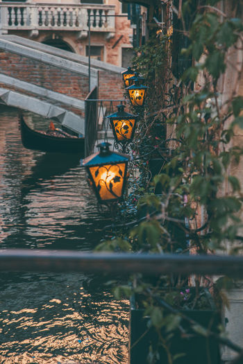 Illuminated lighting equipment on brick wall near water