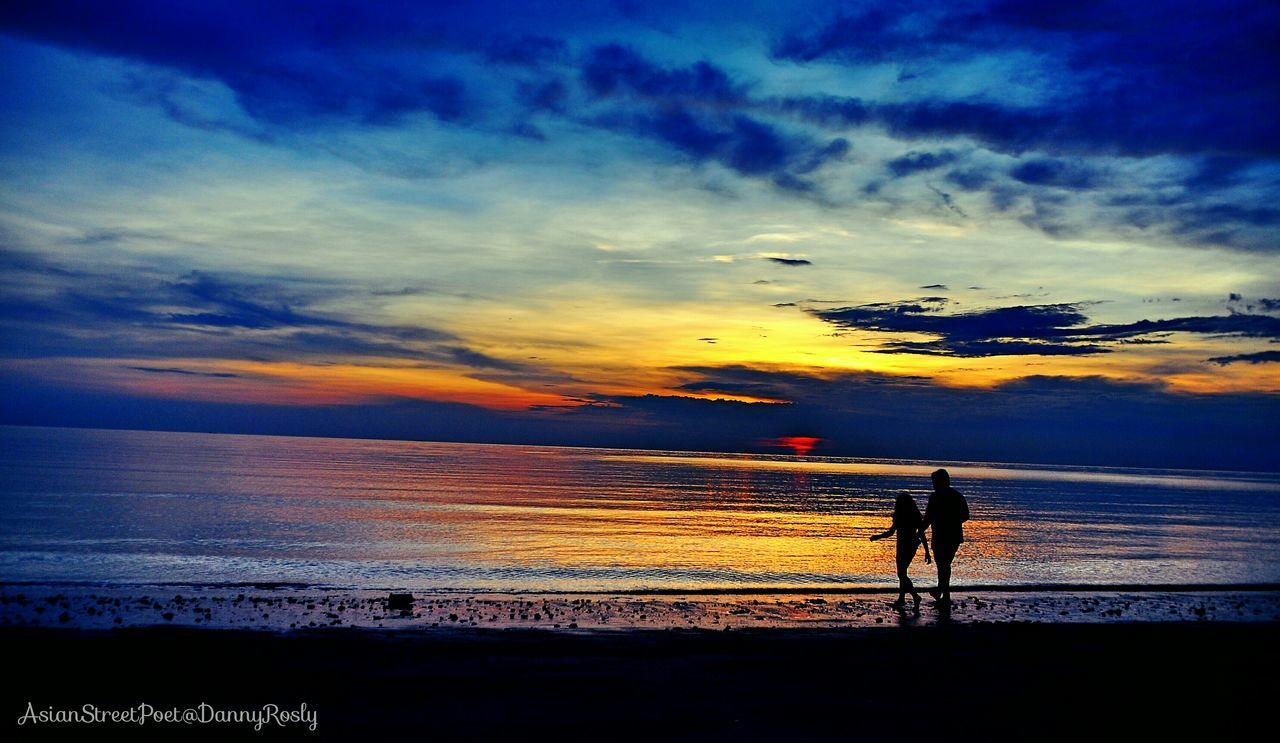 sunset, sea, beach, silhouette, beauty in nature, water, horizon over water, nature, scenics, sky, shore, tranquil scene, real people, cloud - sky, tranquility, one person, idyllic, leisure activity, outdoors, walking, sand, lifestyles, vacations, standing, men, full length, women, people