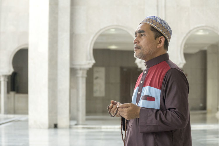 Side View Of Man With Necklace Standing In Mosque