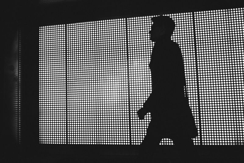 Silhouette man standing against window