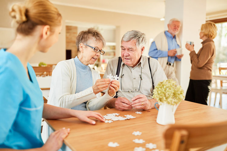 Smiling nurse with senior people playing with jigsaw puzzle at nursing home