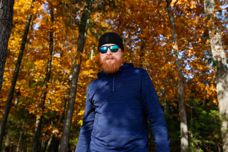 Red headed man with beard on nature hike One Person Tree Focus On Foreground Sunglasses Autumn Casual Clothing Waist Up Outdoors Warm Clothing Front View Nature Hiking Red Beard Redhead Man Males  Hike Hiking Adventures Hiking Adventure Fall Colors Fall Color Autumn colors Autumn Leaves Autumn Collection