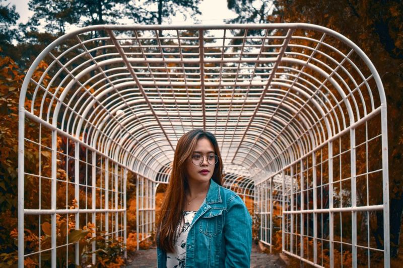 Beautiful young woman against covered walkway