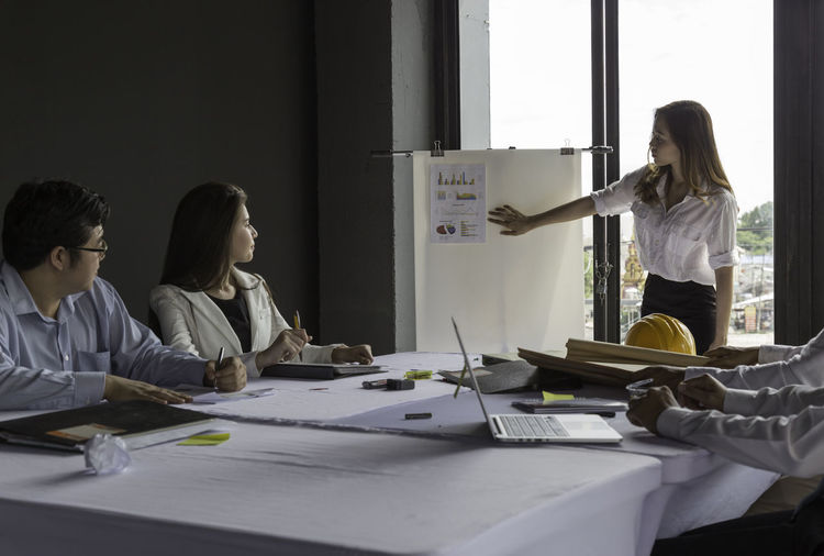 Businesswoman Giving Presentation While Colleagues Sitting At Table In Office