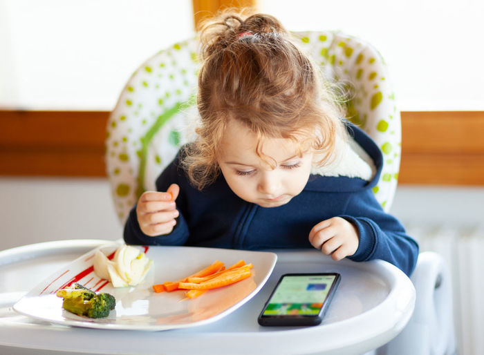 Cute girl eating and looking at mobile phone while sitting on seat at home