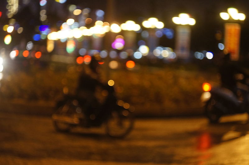 City Focus On Foreground Illuminated Land Vehicle Mode Of Transport Motorcycle Night Outdoors Real People Road Scooter Street Transportation