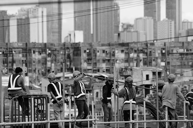 Group of people standing on railing against buildings in city