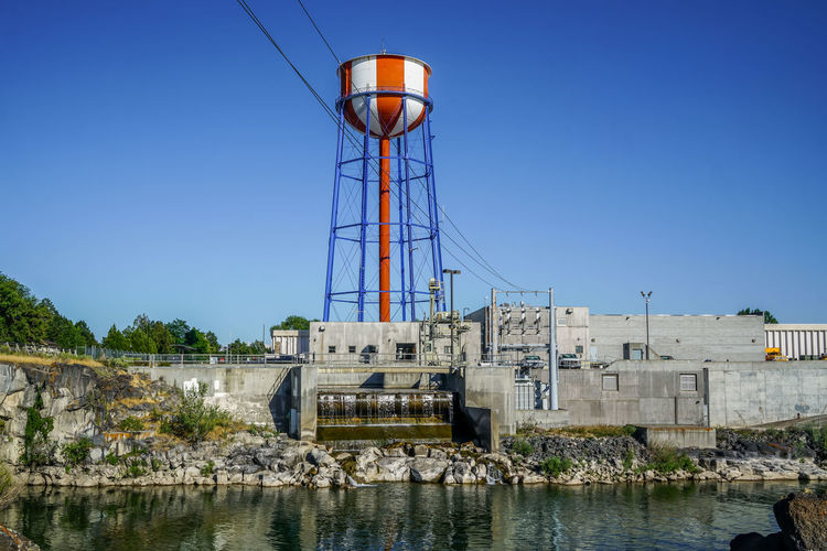 Water tower by river against clear blue sky