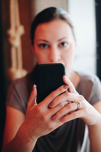 Woman using mobile phone in home
