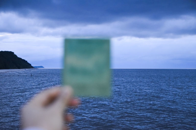 Cropped Image Of Person Holding Photograph Against Baltic Sea