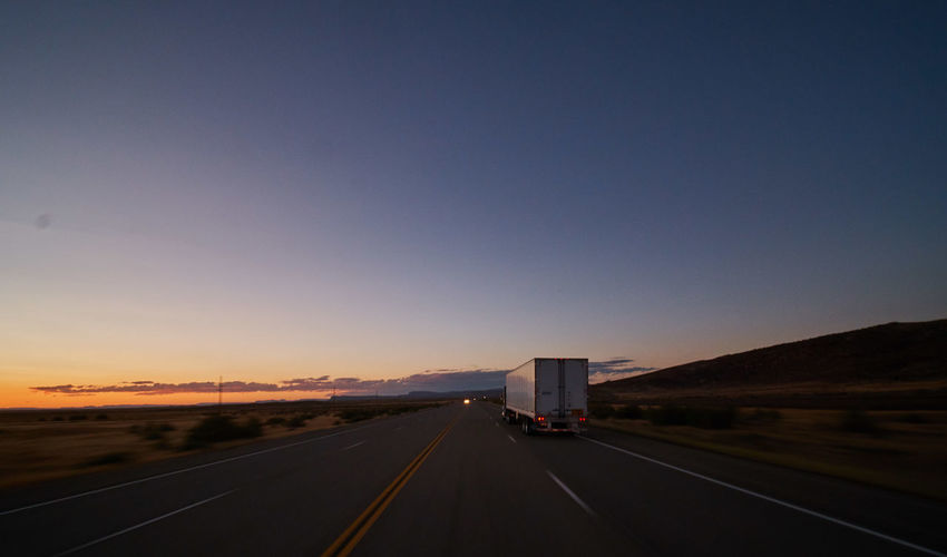Sky Road Transportation Direction Nature The Way Forward Copy Space Land Vehicle Highway Sign Truck Clear Sky Road Marking Mode Of Transportation Diminishing Perspective Marking Symbol vanishing point No People Sunset Outdoors Trucking Dividing Line