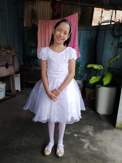Full length portrait of a smiling girl standing outdoors