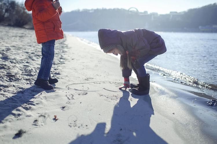Full length of girl making heart shape on sand at beach