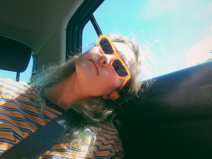 Low angle view of young woman wearing sunglasses sitting in car
