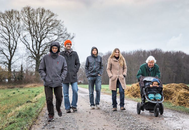 Family walking on road against sky during winter