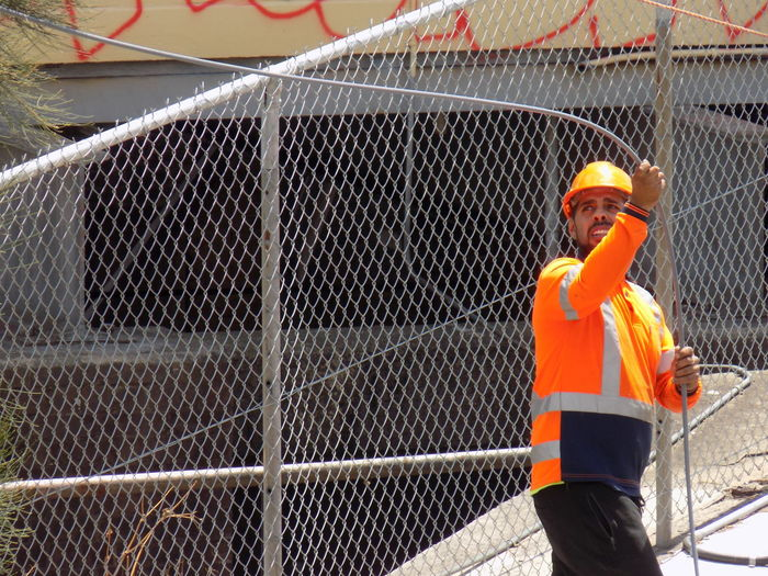 Portrait of man standing by chainlink fence