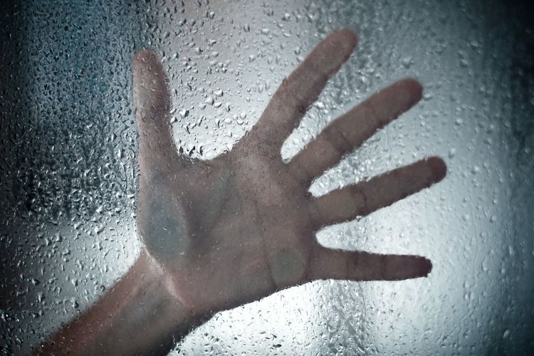 Close-up of human hand on wet glass window