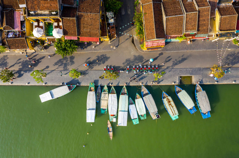 Drone view of boats in river by buildings