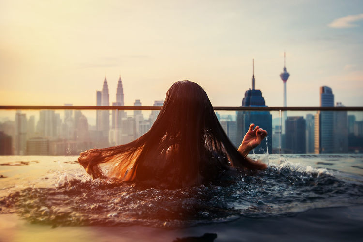 Rear View Of Woman Swimming In Infinity Pool At City