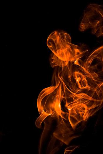 Close-Up Of Orange Smoke Against Black Background