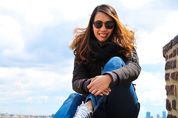 Portrait of happy young woman wearing sunglasses against sky