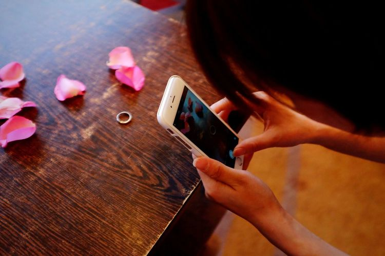 Woman Photographing Ring By Flower Petals Through Smart Phone On Table