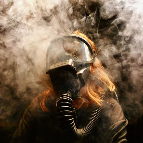 Close-up of woman wearing gas mask in darkroom