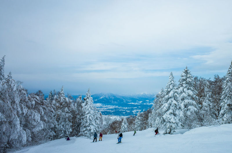 People snowboarding on snow covered landscape against sky