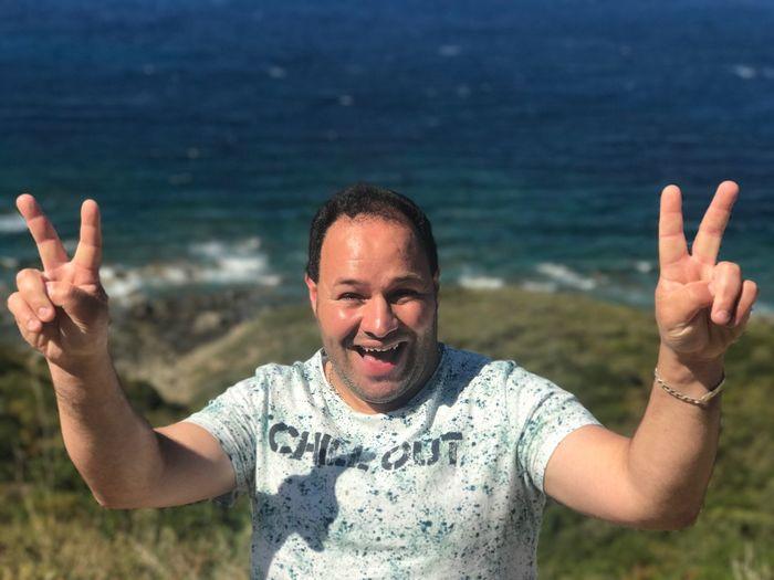 Portrait of cheerful man gesturing peach sign at corsica beach