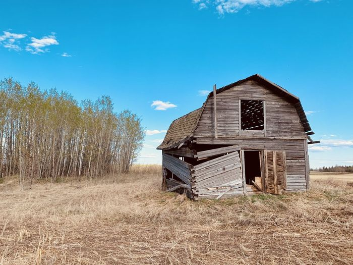 Abandoned house on field against blue sky