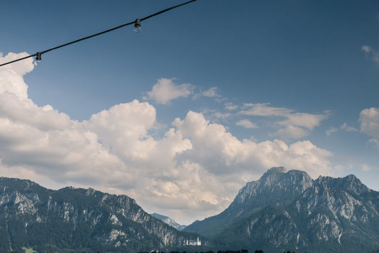 Chain of two light bulbs with a view to the mountain range of castle Neuschwanstein. Allgäu Neuschwanstein Beauty In Nature Bulb Cable Cloud - Sky Cold Temperature Day Low Angle View Mountain Mountain Range Nature No People Nusshain 07 17 Outdoors Scenics Sky Two Of A Kind