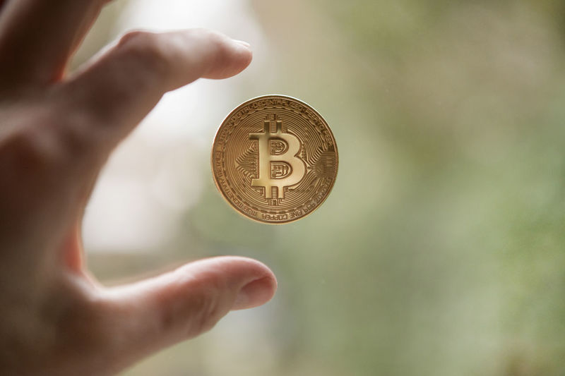 Cropped hand of person reaching bitcoin