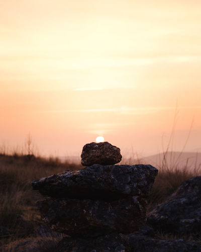 Stack of rocks on field against sky during sunset