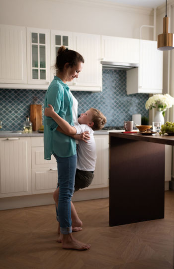 Side view of mother and daughter standing on floor at home