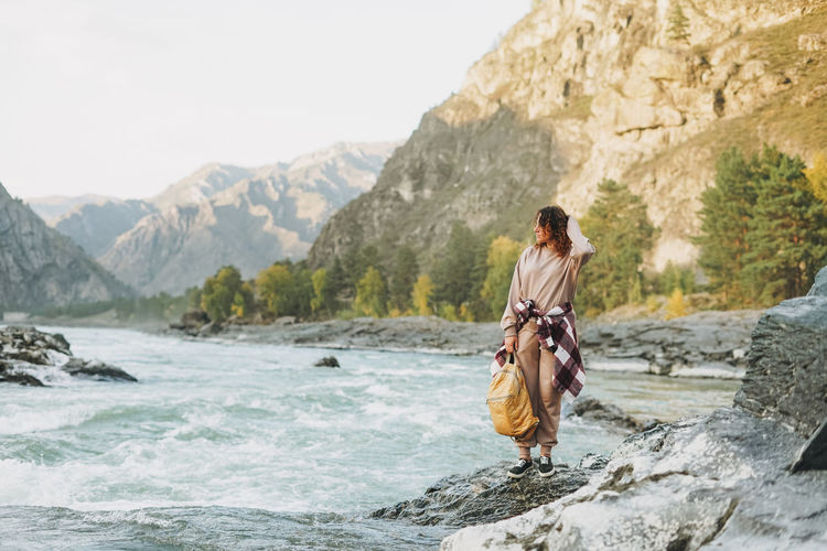 Young woman traveller in casual with backpack on mountain river on the sunset