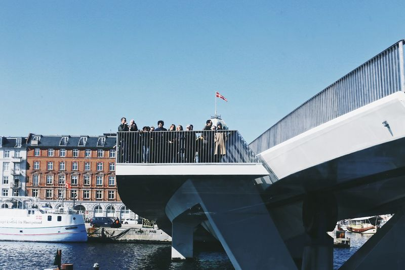 People on a bridge Built Structure Citylife People Full Frame Architecture Built Structure Water Sky Clear Sky Bridge The Art Of Street Photography Day Flag Nature Building Exterior Travel River Connection Bridge - Man Made Structure Waterfront Transportation Outdoors Tourism Passenger Craft