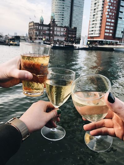 Rotterdam, cheers Human Hand Refreshment Drink Hand Alcohol Food And Drink Glass Celebratory Toast Human Body Part People Friendship Personal Perspective City Real People Holding Outdoors Building Exterior Water Built Structure Architecture