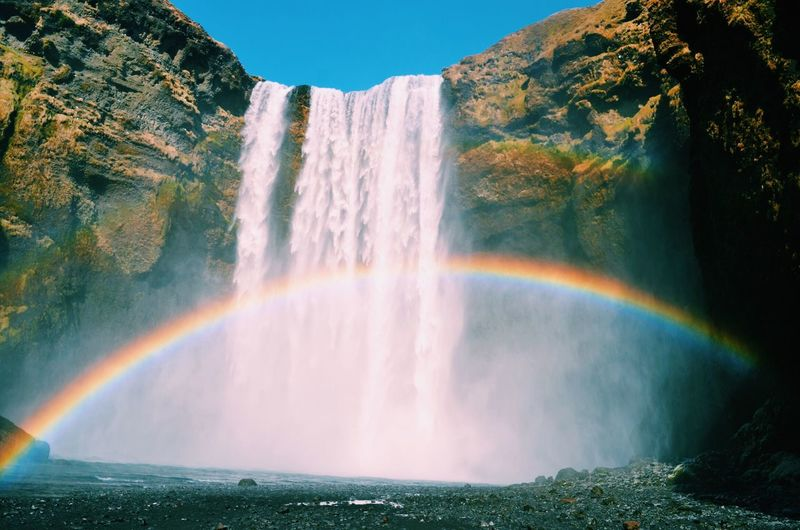 Scenic view of rainbow by waterfall