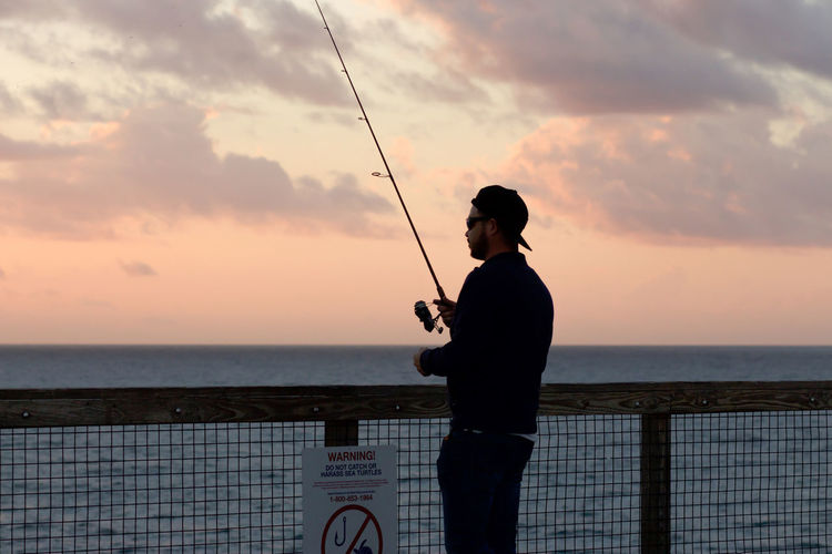 Rear view of man fishing by sea against sky during sunset