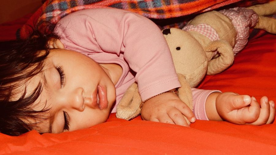 Close-up of baby sleeping on bed at home