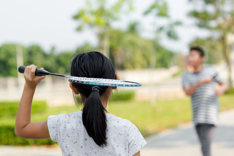 Rear view of girl playing badminton with friend