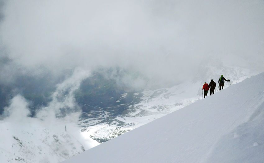Hikers on snow covered mountain against sky