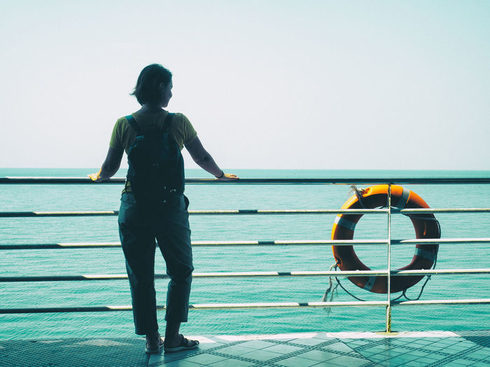 Rear view of woman standing by railing of boat in sea against clear sky