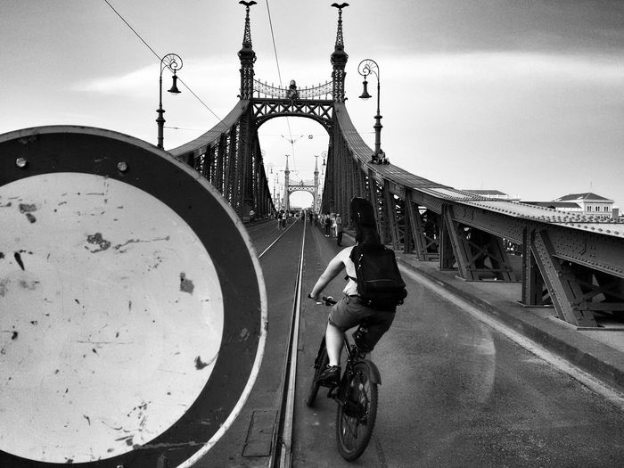 Rear view of people riding bicycle on bridge